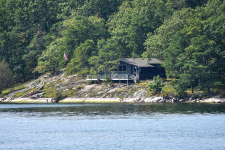 Isolated cottage in a rocky area on the coast of a lake during daytime, and surrounded by trees. Real State concept. Thousands Islands. Ontario, Canada