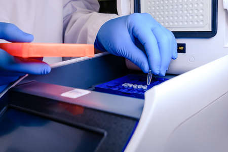 Loading a DNA tube into a PCR (polymerase chain reaction) thermocycler machine in a bioscience laboratory. Concept of science, laboratory and study of diseases.