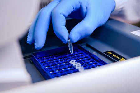 Loading a DNA tube into a PCR (polymerase chain reaction) thermocycler machine in a bioscience laboratory. Concept of science, laboratory and study of diseases. Coronavirus (COVID-19) treatment developing.