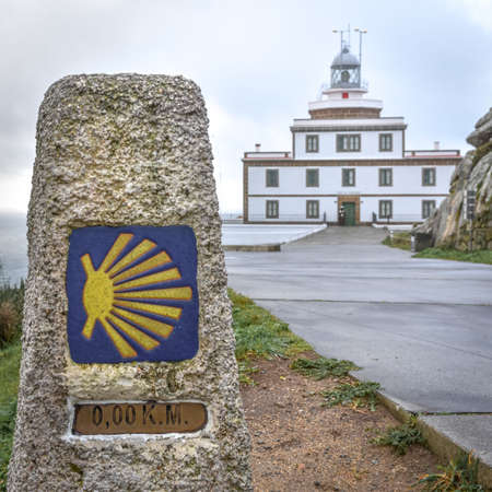 Sign of the Camino de Santiago and Finisterre Lighthouse in the background. In the light of day, in a sky with clouds. Galicia, Spain. Galicia, Spain