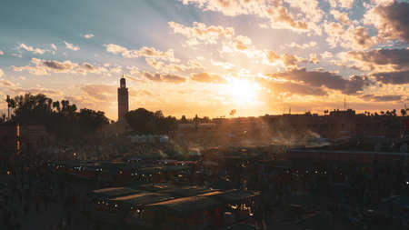 Yamaa el Fna Square with its markets and crowds of people and the tower of the mosque in the background, at sunset. Travel concept. Marrakech, Morocco