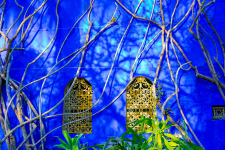 Bright blue wall and complementary yellow windows in the Jardin Majorelle Concept of travel and architecture. Marrakech, Morocco