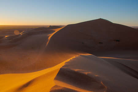 Wide angle shoot of sand desert dunes of Erg Chigaga moved by the wind. The gates of the Sahara, at sunrise. Morocco. Concept of travel and adventure Stockfoto