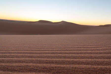 Close-up desert dunes of Erg Chigaga, at the gates of the Sahara, at sunrise. Morocco. Concept of travel and adventur