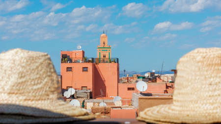 Typical colorful buildings of the Marrakesh medina on a sunny day with a blue sky and some clouds. Hats out of focus in the foreground. Travel concept. Marrakech, Morocco