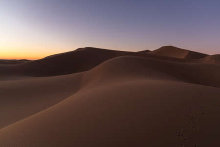 Dreamy desert concept at Twilight of dawn at desert dune of Erg Chigaga, at the gates of the Sahara. Morocco. Concept of travel and adventure