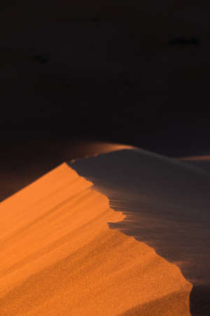 Close-up of sand desert dunes of Erg Chigaga moved by the wind. The gates of the Sahara, at sunrise. Morocco. Concept of travel and adventure