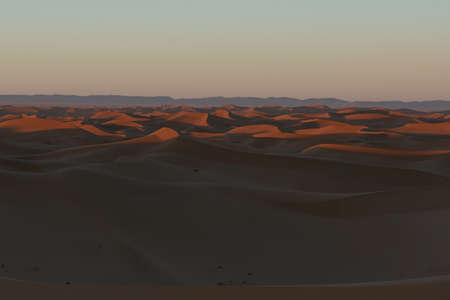 Huge desert dunes of Erg Chigaga, at the gates of the Sahara, at sunrise. Morocco. Concept of travel and adventure.
