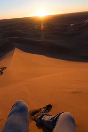 Legs of unrecognizable man from the top of a dune at sunrise, in Erg Chigaga, Morocco