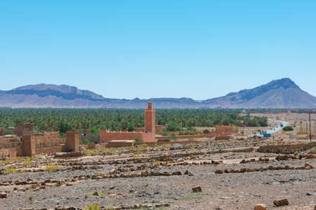 buildings in the foreground and palm forest and mountains of the Draa Valley, Zagora, Morocco. Stockfoto