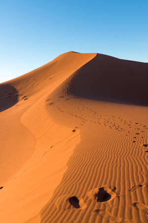 Wide angle shoot of footpath in desert dunes of Erg Chigaga.The gates of the Sahara, at sunrise. Morocco. Concept of travel and adventure Stockfoto