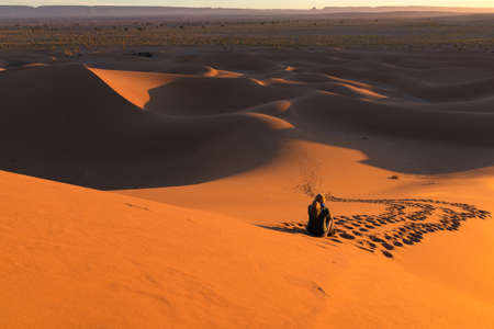 High angle shot of unrecognizable lonely woman in the desert dunes of Erg Chigaga, at the gates of the Sahara, at sunrise. Morocco. Concept of travel and adventure