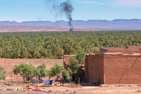 house in the foreground and palm forest and mountains of the Draa Valley, Zagora, Morocco. Bonfire smokes in the background.