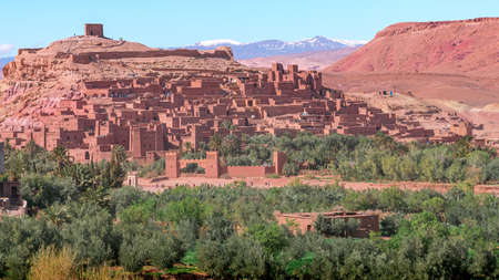 Daytime wide angle shot of Ksar de Ait Ben Haddou, with its abobe houses and towers, surrounded by palm trees and with the Atlas Mountains in the background, Morocco. Stockfoto
