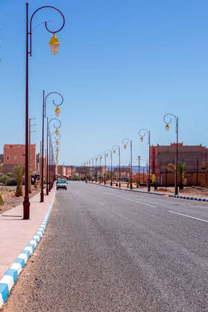 Wide angle shot of buildings, street lamps and road of the town of Tagonite in Draa Valley, Morocco