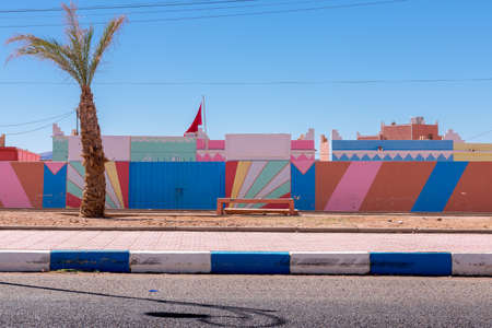 Wide angle shot colorful buildings and palm tree in the town of Tagonite in Draa Valley, Morocco
