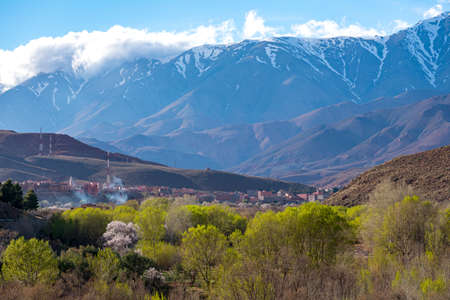 Daytime wide angle shot of Beautiful landscape of snow capped mountains and bushes and a village in the valley. Atlas, Morocco.