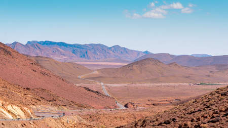 Otherworldly Landscape with mountains and reddish land and infinite road that crosses them. High Atlas, Morocco. Stockfoto