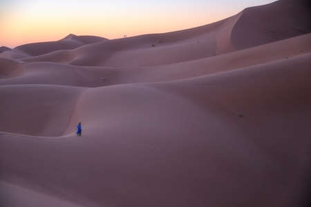 Unrecognizable Berber man walking on a dreamy desert at Twilight of dawn. Desert dune of Erg Chigaga, at the gates of the Sahara. Morocco. Concept of travel and adventure. Stockfoto