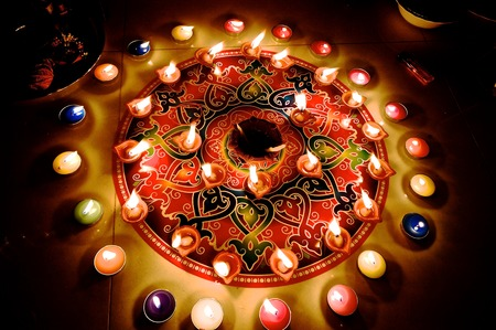 A colorful rangoli with candle and diya burning for christmas and diwali celebration