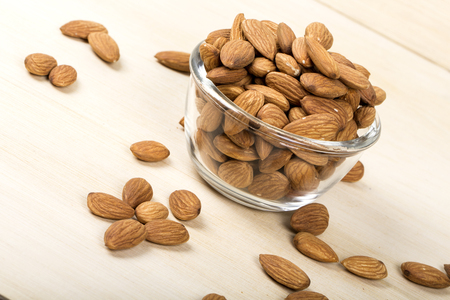 Almonds in bowl on wooden background, group of almonds, sackcloth 版權商用圖片