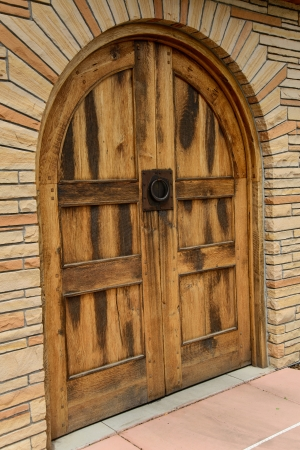 The weathered look of the wood door with a rustic metal handle awaits visitors to the winery  Stock Photo
