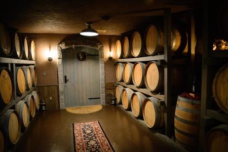 The dimly lit room elegantly shines upon stacked oak wine barrels stock photo
