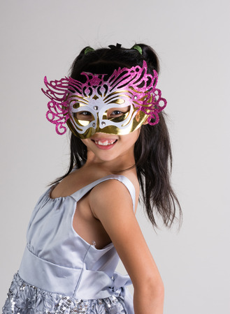 Cute, cheerful little girl in mask, nice dress ready for holiday party Stock Photo