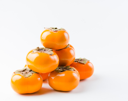 Small stack of ripe, delicious, fresh, organic Fuyu Persimmon Stock Photo - 23116758