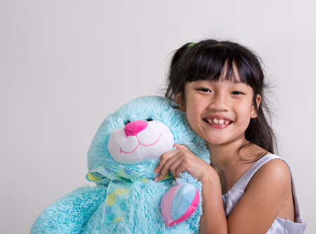Cute, cheerful little girl holding a blue bunny Stock Photo - 23116761