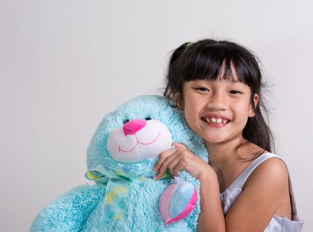 Cute, cheerful little girl holding a blue bunny Stock Photo - 23116761