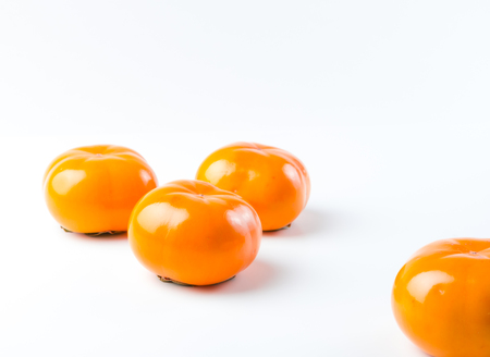 Ripe, fresh, delicious, organic Fuyu Persimmon on white background