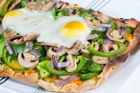 Fresh, hot baked Vegetarian flatbread pizza with 2 eggs sunny side-up