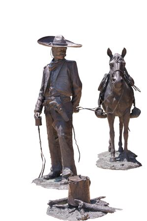 Public statue of bronze cowboy and horse at camp isolated background
