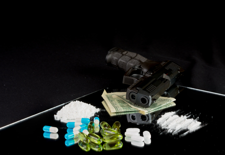 Life is at the edge  Gun, pills, drugs, money on black background
