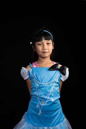 Cute, cheerful little girl posing on black background