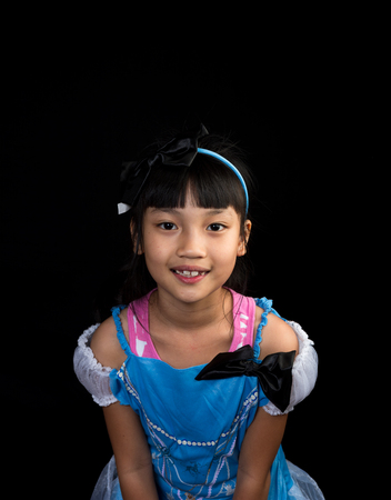 Cute, cheerful little girl staring on black background