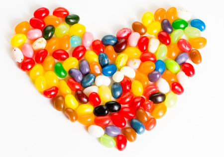 Colorful, mixed jelly beans in heart shape on white background