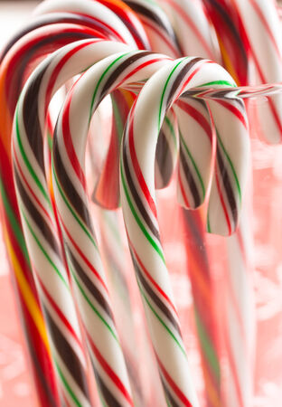 Candy canes hanging around the glass Stock Photo