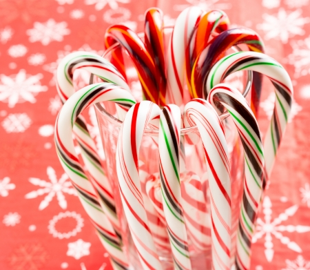 Candy canes forming flower ring on decorative red background