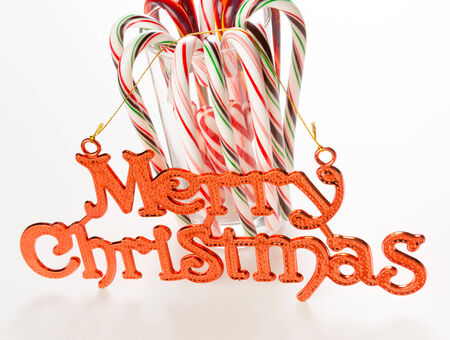 Candy canes with Merry Christmas sign on white background