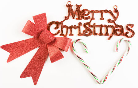Merry Christmas sign with red bow and candy cane on white background Stock Photo