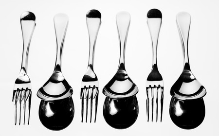 Set of stainless steel fork and spoon reflection on white