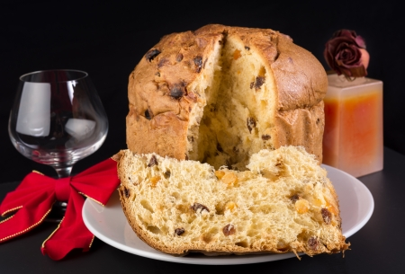 Delicious panettone, Christmas cake with glass of wine, candle, and scented candle