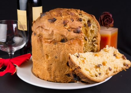 Delicious whole panettone, Christmas cake with glass, bottle of red wine, and scented candle