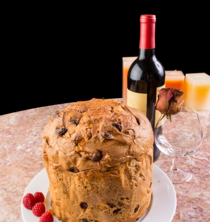 Delicious whole panettone, Christmas cake with glass, bottle of red wine, and candles Stock Photo