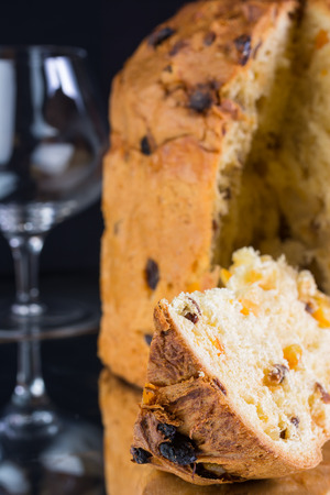 Delicious whole panettone with a slice, Christmas cake with glass of wine