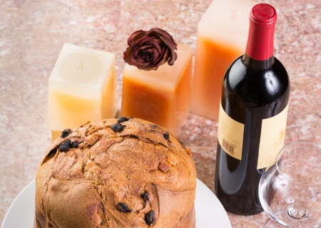 Delicious whole panettone, Christmas cake with glass, bottle of wine, candles and dried rose bud