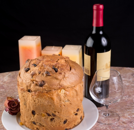 Delicious whole panettone, Christmas cake with glass, bottle of wine, candles