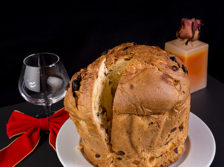 Delicious whole panettone, Christmas cake with glass of wine, candle and dried rose bud